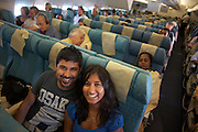 Honeymoon couple on their return home after a holiday in the Maldives return home in economy class, grinning.