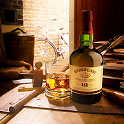 Whiskey Bottle and filled glass in a workshop surrounded by tools and a bike in the background Ray Massey is an established, award winning, UK professional  photographer, shooting creative advertising and editorial images from his stunning studio in a converted church in Camden Town, London NW1. Ray Massey specialises in drinks and liquids, still life and hands, product, gymnastics, special effects (sfx) and location photography. He is particularly known for dynamic high speed action shots of pours, bubbles, splashes and explosions in beers, champagnes, sodas, cocktails and beverages of all descriptions, as well as perfumes, paint, ink, water – even ice! Ray Massey works throughout the world with advertising agencies, designers, design groups, PR companies and directly with clients. He regularly manages the entire creative process, including post-production composition, manipulation and retouching, working with his team of retouchers to produce final images ready for publication.