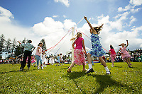 Young dancers dancing around a maypole help to celebrate the annual empire day's celebration in Cumberland.  Comox Valley, Vancouver Island, British Columbia, Canada.