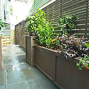 Small narrow garden for entertainment with cutom furniture and horizontal lattice fence
