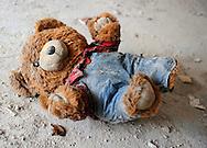 A teddy bear lies in the dust.