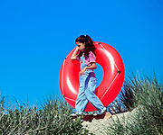 Girl with innertube float on the way to the beach, Outer Banks, North Carolina.