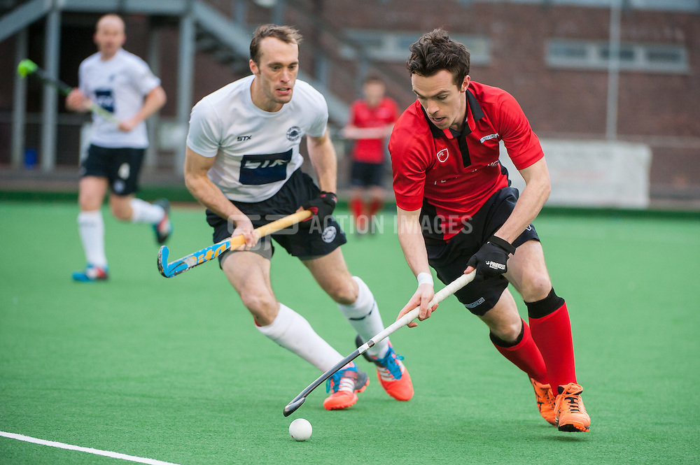 Southgate's Sam Mee goes round Tim Deakin of East Grinstead. Southgate v East Grinstead - Now: Pensions Hockey League Premier Division, Trent Park, London, UK on 01 February 2015. Photo: Simon Parker