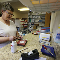 Jeanie Lee counts out pills for a patient at the Good Samaritan Free Clinic in Tupelo.