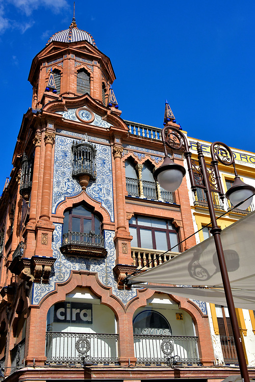 Pedro Rold&aacute;n Building at Plaza del Pan in Seville, Spain<br /> It is easy to hustle through Seville squares and be oblivious to their history. This plaza is a great example. Beginning in the 13th century, it was filled with stalls selling bread and pastries. Plaza del Pan (Bread Square) eventually became the center for the Bakers Guild. They were evicted in 1820 in favor of an urban development project. From 1868 until 1971, it was called Commerce Square. Now its official name is Plaza of Jesus of the Passion. But Spanish legacies die hard. The locals still call it Plaza del Pan. The visual highlight is the Pedro Rold&aacute;n Building. Architect Jos&eacute; Espiau y Mu&ntilde;oz crafted his version of Regionalist architecture in 1925 featuring blue ceramic tiles on the fa&ccedil;ade and dome.