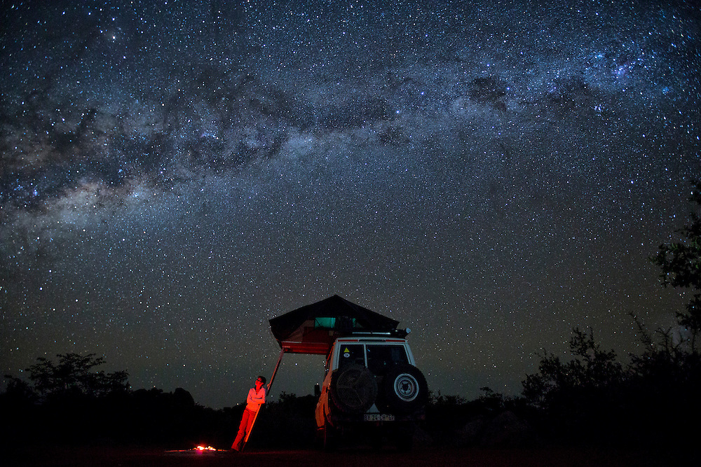A woman stands under the stars next to her 4x4 vehicle, her tent,  and a campfire.
