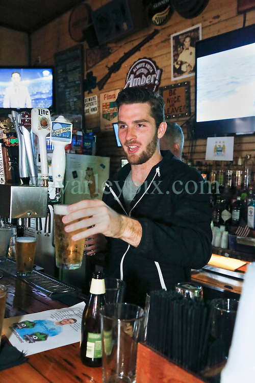 23 November 2015. Finn McCool's Irish Pub, New Orleans, Louisiana.<br /> Major League Soccer (MLS) star player Patrick Mullins of New York City FC serves a few pints to customers from behind the bar.<br /> Photo&copy;; Charlie Varley/varleypix.com