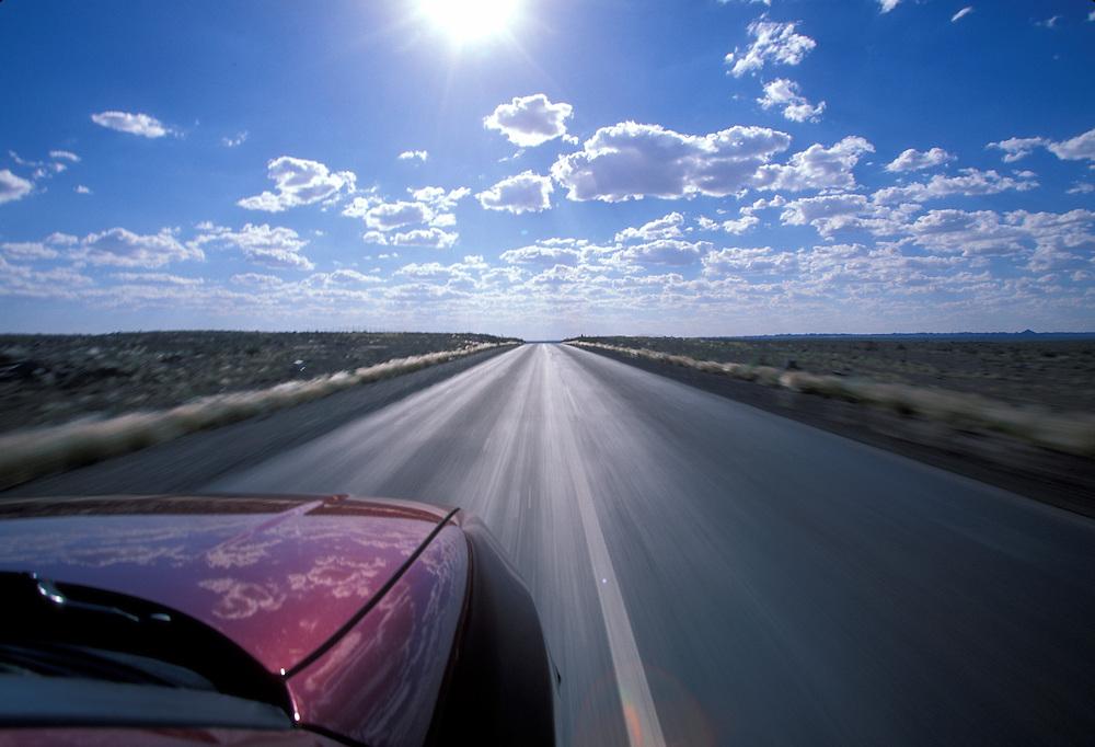 Namibia, Car speeds along highway in southern Namib desert.