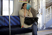 woman doing her make up while sitting in a train
