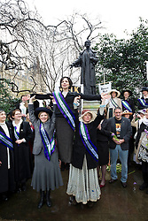 © Licensed to London News Pictures. 08/03/2013. London, UK. Women dressed as suffragettes are seen in front of a statue of Emily Pankhurst after walking to Parliament on International Women's Day in London today (08/03/2013). The end of the walk, which coincides with International Women's Day, launches poverty charity Care International's 'Walk in Her Shoes Campaign', which encourages women to put themselves the shoes of women in the developing world. Photo credit: Matt Cetti-Roberts/LNP