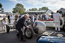 **CAPTION CORRECTION. Picture originally sent with wrong date. Picture was taken TODAY 11/09/2015** © licensed to London News Pictures. 11/09/2015<br /> Goodwood Revival Weekend, Goodwood, West Sussex. UK.<br /> The Goodwood Revival is the world's largest historic motor racing event. Competitors and enthusiasts dress in period fashions recreating the glorious days of the race circuit.<br /> Pictured. Classic cars enter the paddock area.<br /> <br /> Photo credit : Ian Whittaker/LNP