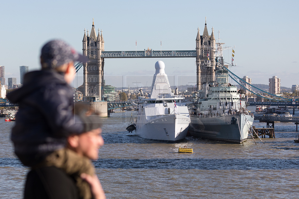 © Licensed to London News Pictures. 22/10/2018. London, UK.  A child sitting on a man's shoulders looks at the Dutch Offshore Patrol Vessel, HNLMS Zeeland (P841) after it arrives in London and moors next to HMS Belfast in front of Tower Bridge on the River Thames this afternoon ahead of a Dutch Royal state visit. Their Majesties King Willem-Alexander and Queen Máxima of the Netherlands will arrive in the UK tomorrow, 23rd October for their first State Visit and will visit HMS Belfast and HNLMS Zeeland, moored alongside. This visit will celebrate 45 years of cooperation between the Royal Netherlands Marine Corps and the Royal Marines.  Photo credit: Vickie Flores/LNP