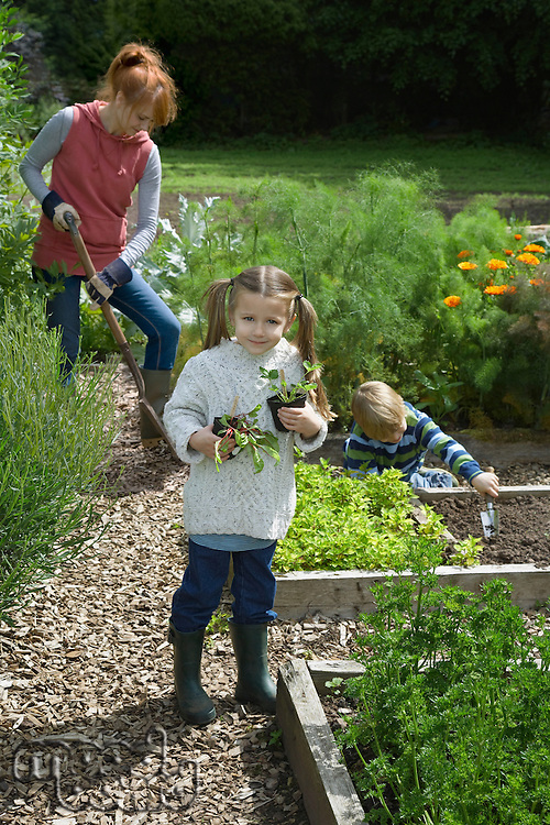 Mother gardening with two children (5-6) in countryside