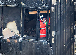 © Licensed to London News Pictures. 18/06/2017. London, UK. A member of London Fire Brigade's Urban Search and Rescue Team installs wooden beams on the 11th floor of the fire ravaged Grenfell tower block. The blaze engulfed the 27-storey building killing dozens - with 34 people still in hospital, many of whom are in critical condition. The fire brigade say that they don't expect to find anyone else alive. Photo credit: Peter Macdiarmid/LNP