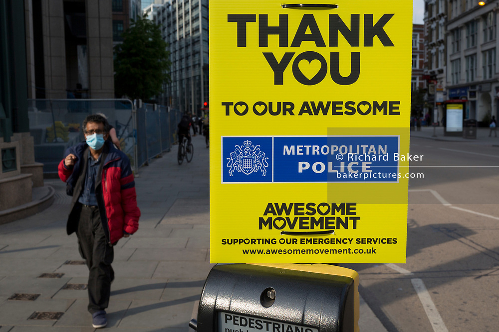 With the Coronavirus lockdown continuing into the Bank Holiday weekend, when Prime Minister Boris Johnson is due to tell the nation that only a gradual easing of regulations and social distancing rules are still to be in place, a person wearing a surgical mask walks towards a sign that supports emergency services workers such as the police has been attached to a crossing post in the City of London, the capital's financial district, on 7th May 2020, in London, England.