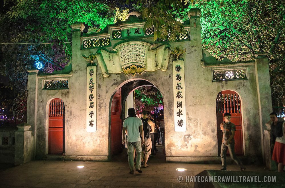 Tourists walk through the stone gate on the shoreline leading to the Temple of the Jade Mountain and The Huc Bridge at night.
