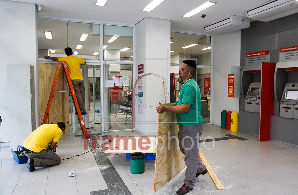 Homens trabalhando na colocação de tapumes na agencia do Baco Santander onde ouve uma tentativa de roubo à caixa eletrônico que  acabou com a troca de tiros entre policiais militares e bandidos armados de fuzil na região da Rua Barão de Tefé, atrás do Shopping West Plaza, na zona oeste de São Paulo, no início da manhã desta terça-feira (25). Nenhum bandido foi preso e pelo menos um policial ficou ferido por estilhaços e varios buracos de balas snao vistos no local Foto Marcelo D. Sants/FramePhoto.