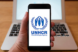 Using iPhone smartphone to display logo of UNHCR