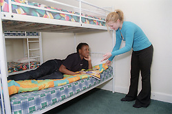Two teenage girls arguing over sleeping bag in dormitory at youth hostel,