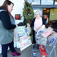 "Hannah Maharrey, Homelessness Prevention and Outreach Director at The Family Resource Center in Tupelo, takes bags of food from Bridgett Nichols, of Belden, during the ""Help Fill Our Van"" food drive project Wednesday afternoon at the Kroger location at crosstown in Tupelo. The food drive will will return on Friday from 1-6."