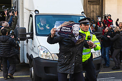 © Licensed to London News Pictures. 11/04/2019. London, UK. A supporter of Wikileaks founder Julian Assange is tackled by police after she jumped in front of a van believed to contain Assange as it leaves Westminster Magistrates Court. Photo credit: Rob Pinney/LNP