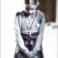 Young girl standing alone looking down