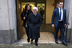 © Licensed to London News Pictures. 11/01/2018. London, UK. Bernie Ecclestone (centre) leaves the High Court with his wife Fabiana Flosi during a hearing over his daughter Petra Ecclestone's legal battle with ex-husband James Stunt following their £5.5billion divorce. Photo credit: Rob Pinney/LNP