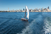 "The sloop ""Joy Ride"" passes behind the Seattle to Bainbridge Island ferry as it leaves the city."