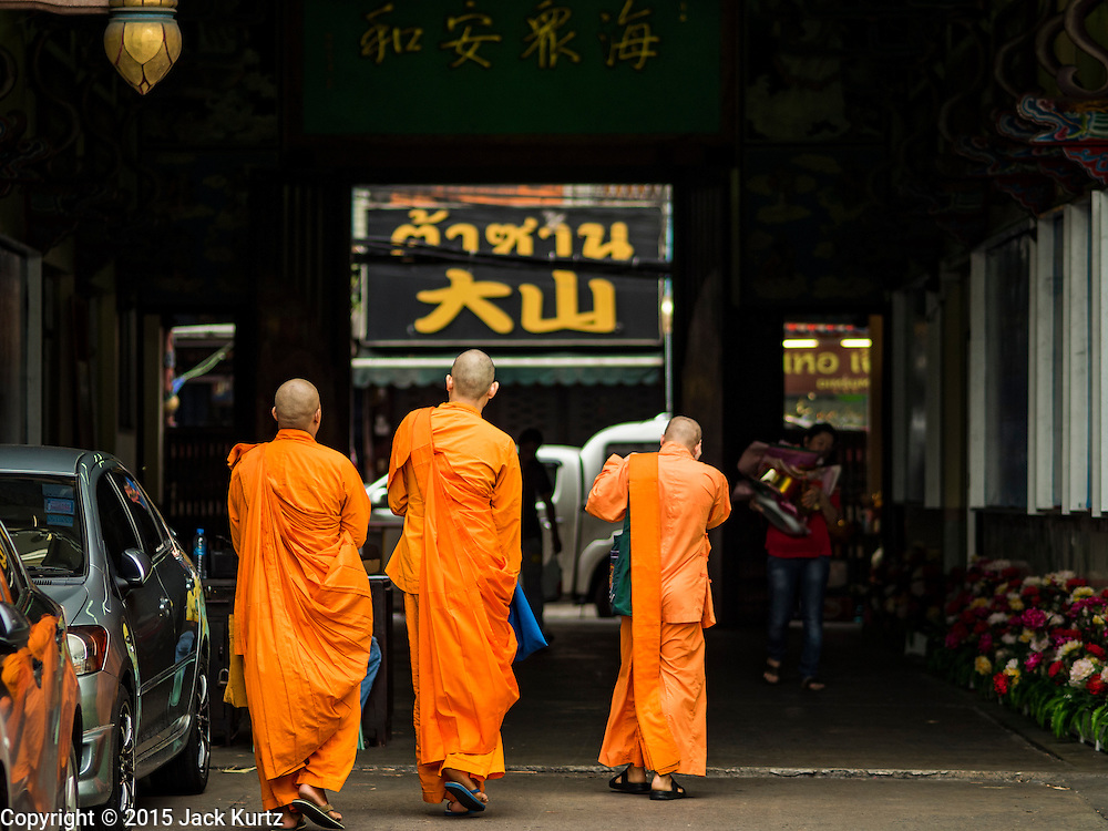 28 AUGUST 2015 - BANGKOK, THAILAND: Mahayana monks walk out of Wat Mangkon Kamalawat in the Chinatown section of Bangkok on Hungry Ghost Day. Wat Mangkon Kamalawat is the largest Mahayana Buddhist temple in Chinatown. Mahayana  Buddhists believe that the gates of hell are opened on the full moon of the seventh lunar month of the Chinese calendar, and the spirits of hungry ghosts allowed to roam the earth. These ghosts need food and merit to find their way back to their own. People help by offering food, paper money, candles and flowers, making merit of their own in the process. Hungry Ghost Day is observed in communities with a large ethnic Chinese population, like Bangkok's Chinatown.     PHOTO BY JACK KURTZ
