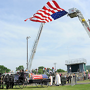 A horse draw carriage carrying the casket of Army Sergeant Devin Snyder rolls under a large American flag that was draped between  fire trucks from Wayland and Dansville during Saturday morning's funeral service