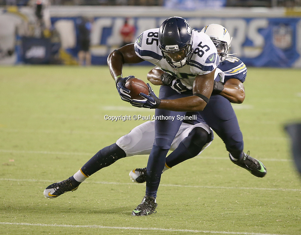 Seattle Seahawks tight end Anthony McCoy (85) gets tackled by San Diego Chargers rookie defensive back Gordon Hill (41) after catching a pass with 28 seconds left in the fourth quarter during the 2015 NFL preseason football game against the San Diego Chargers on Saturday, Aug. 29, 2015 in San Diego. The Seahawks won the game 16-15. (©Paul Anthony Spinelli)
