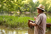 A fly fisherman casts for smallmouth bass on the Olentangy River in Central Ohio.  His handmade wooden canoe is seen beeched on the bank behind him.