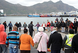 Cape Town - 180813 - The Hout Bay fishing community are distraught and tensions are running high after an alleged poacher was shot at see while being apprehended by the authorities In pic the family and friends say a prayer at the water's edge before the divers set out to find the missing man  Photographer - Tracey Adams - ANA African News Agency