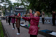 Locals practice tai chi early in the morning beside Hoan Kiem Lake, Hanoi, Vietnam, Southeast Asia