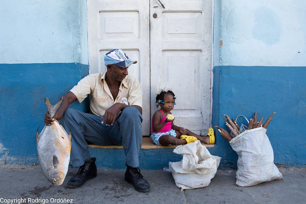 A man holding a fish looks on as a girl eats an orange, near a traditional market in Santiago de Cuba, Cuba, on December 27, 2014.