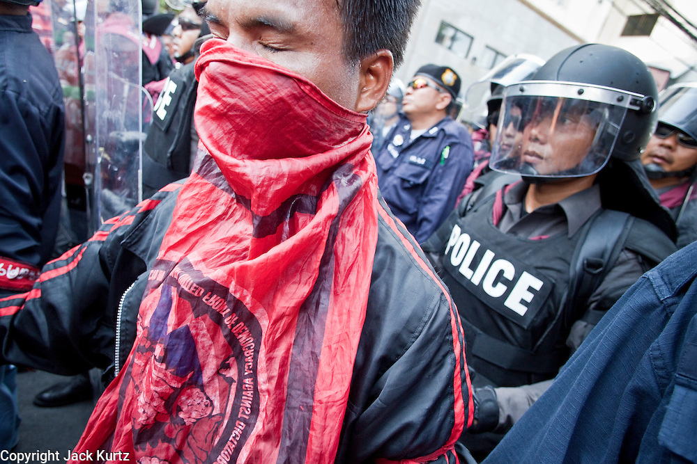 Apr. 12, 2010 - BANGKOK, THAILAND: Red Shirt security guards protect Thai police and try to hold back the crowd in front of the Prime Minister's house on Soi 31 off of Sukhumvit Rd in Bangkok Monday. The funeral cortege for the Red Shirts killed in the violent crackdown Saturday wound through Bangkok and parts of the procession passed by the Prime Minister's home. Thousands of mourners came out to pay respects for dead Red Shirts. 21 people, including 16 Thai civilians were killed when soldiers tried to clear the Red Shirts' encampment in Bangkok. Thousands more came out to call for the government of Thai Prime Minister Abhisit Vejjajiva to step down. Today Gen. Anupong Paojinda, the Chief of Staff of the Thai Army, reiterated that the Army would not use violence to break up the protests and joined the call for the Prime Minister to call new elections. This is the beginning of Songkran, Thai New Year's week, and the government has cancelled the official festivities fearing more violence. It was during last year's Songkan festivities that the Thai Army and police used force to break up the Red Shirt protests. That protest is now called the Songkran Riots.         Photo By Jack Kurtz