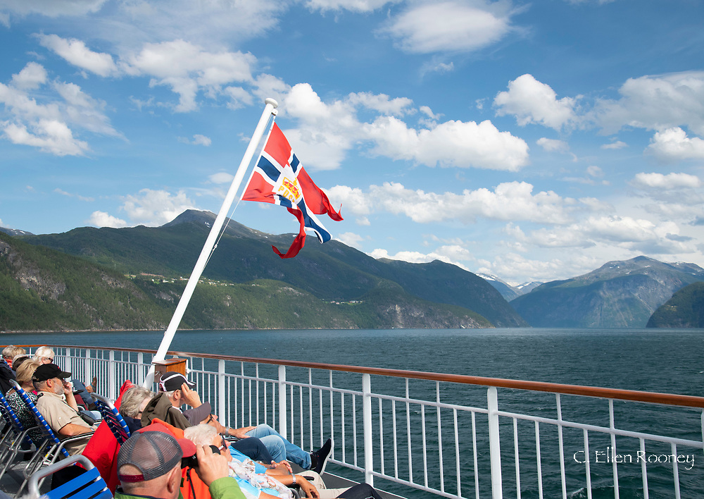 Passengers enjoying the scenery on Geiranger Fjord during a Hurtigruten cruise.  Geiranger, Vesetlandet, Norway