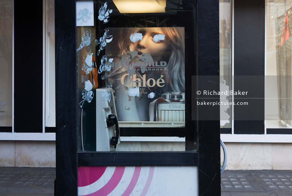 The eyes of an ad model are obscured by daubs of paint on a phone kiosk window.
