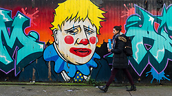 © Licensed to London News Pictures. 11/02/2020. London, UK. A woman walks past graffiti depicting Prime minister Boris Johnson as a clown, near Brick Lane in London. Photo credit: Vickie Flores/LNP