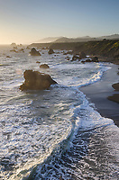Waves crashing against sea stacks and sand beach on Sonoma Coast California
