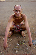 A 78 year-old man is sitting on a street in Chork Village, Cambodia.