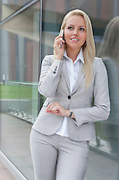 Beautiful young businesswoman conversing on cell phone while leaning on glass wall