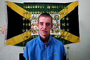 A young scally called Rob Sitting in his bedroom infront of his Jamaica flag and ganja draips, Aberdeen, Scotland, UK 2004