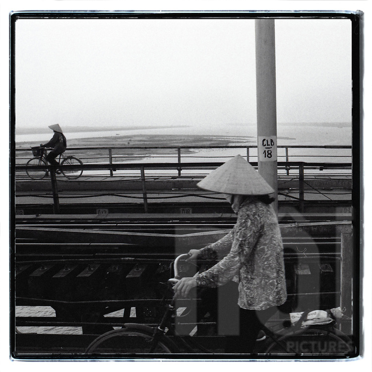 Two Vietnamese women wearing conical hats ride their bicycles across the Long Bien bridge on opposite sides. The Red River is visible in the background, Hanoi, Vietnam, Southeast Asia