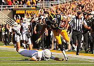 September 21 2013: Iowa Hawkeyes wide receiver Kevonte Martin-Manley (11) is tripped up by Western Michigan Broncos punter J. Schroeder (37) as he returns a punt during the first quarter of the NCAA football game between the Western Michigan Broncos and the Iowa Hawkeyes at Kinnick Stadium in Iowa City, Iowa on September 21, 2013.