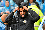 Manchester City manager Pep Guardiola wearing a waterproof coat and hood to protect himself from the rain before the Premier League match between Cardiff City and Manchester City at the Cardiff City Stadium, Cardiff, Wales on 22 September 2018.