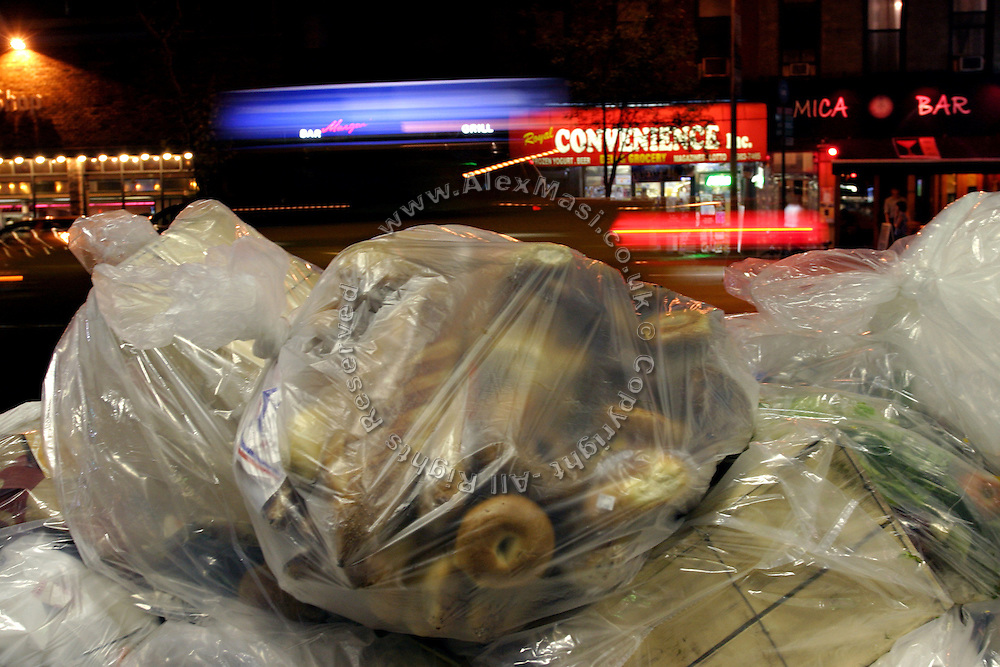 A bag full of bagels and bread just before the arrive of the Freegans in one of the numerous dump sites in Manhattan, New York, NY., on Wednesday, July 19, 2006. Freegans are a community of people who aims at recovering wasted food, books, clothing, office supplies and other items from the refuse of retail stores, frequently discarded in brand new condition. They recover goods not for profit, but to serve their own immediate needs and to share freely with others. According to a study by a USDA-commissioned study by Dr. Timothy Jones at the University of Arizona, half of all food in the United States is wasted at a cost of $100 billion dollars every year. Yet 4.4 million people in the United States alone are classified by the USDA as hungry. Global estimates place the annual rate of starvation deaths at well over 8 million. The massive waste generated in the process fills landfills and consumes land as new landfills are built. This waste stream also pollutes the environment, damages public health as landfills chemicals leak into the ground, and incinerators spew heavy metals back into the atmosphere. Freegans practice strategies for everyday living based on sharing resources, minimizing the detrimental impact of our consumption, and reducing and recovering waste and independence from the profit-driven economy. They are dismayed by the social and ecological costs of an economic model where only profit is valued, at the expense of the environment. In a society that worships competition and self-interest, Freegans advocate living ethical, free, and happy lives centred around community and the notion that a healthy society must function on interdependence. Freegans also believe that people have a right and responsibility to take back control of their time.