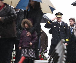 February 21, 2011: A police officer is seen saluting the casket of deputy U.S. marshal Derek Hotsinpiller at the burial site in the Bridgeport Cemetery.  (Photo by: Ben Queen)