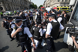 © Licensed to London News Pictures. 21/06/2017. London, UK. Police officers hold a man on the floor as they make an arrest at the 'Day of Rage' protest in Parliament Square. The demonstration is calling for justice for the victims of the Grenfell Tower fire. Photo credit: Rob Pinney/LNP