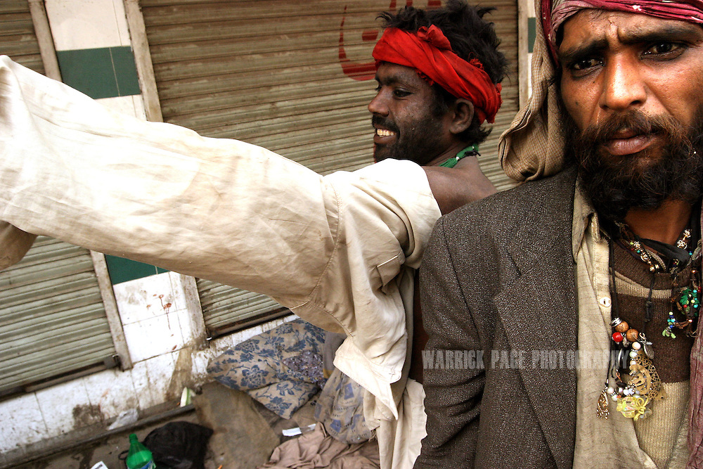 "A heroin user puts on his ""shawal kameez"" after waking on the streets of the Old City and preparing to search for his first 'fix'. Heroin is cheap and readily available in Pakistan due to it's proximity to Afghanistan which supplies almost 90% of heroin to Europe, December 11, 2004, Lahore, Pakistan. Almost 20% of heroin produced in Afghanistan is trafficked through Pakistan according to the UN Office on Drugs and Crime (UNODC). With the fall of the Taliban, opium cultivation has risen dramatically in spite of Afghan and coalition forces attempts to stem production. Pakistan has between 3.5-4 million heroin users, one of the highest numbers of heroin users in the world, next to Iran. (Photo by Warrick Page)"